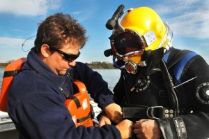 effrey Pardee, Panamerican diver tender, examines diver James Duff's equipment and topside air supply during an initial dive event Jan. 22, 2015, on the Savannah River near Old Fort Jackson. Duff, a Panamerican diver and maritime archaeologist, used a rope to connect sections of the CSS Georgia wreck site scuttled on the river floor. A network of ropes connects wreck site artifacts and assists divers to navigate through the murky underwater floor of the Savannah River. CSS Georgia recovery is the first action begun under the construction phase of the Savannah Harbor Expansion Project (U.S. Army Corps of Engineers photo by Chelsea Smith.)
