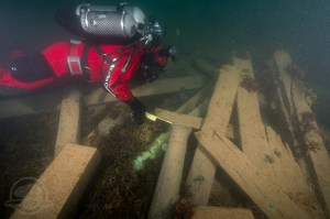Astern of the wreck, Parks Canada underwater archaeologist Filippo Ronca measures the muzzle bore diameter of one of two cannons found on the site, serving to identify this gun as a brass 6-pounder.  @ Thierry Boyer / Parks Canada