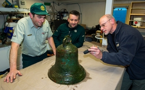 Parks Canada's Ryan Harris (left) and Jonathan Moore (middle) examine the ship's bell with Government of Nunavut archaeologist Dr. Douglas Stenton (right).  © Parks Canada / Thierry Boyer