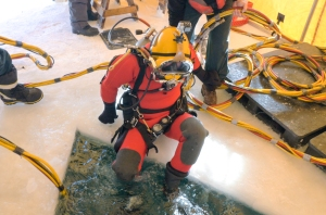 Wearing an insulated diving suit and hooked up to a surface supply of oxygen, a member of the Parks Canada Underwater Archaeology Team prepares to enter the water during a training session.  Copyright Parks Canada